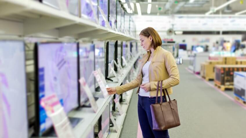 woman chooses a TV in the store.