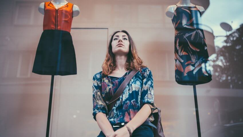 Unhappy young woman standing in front of the clothing store.