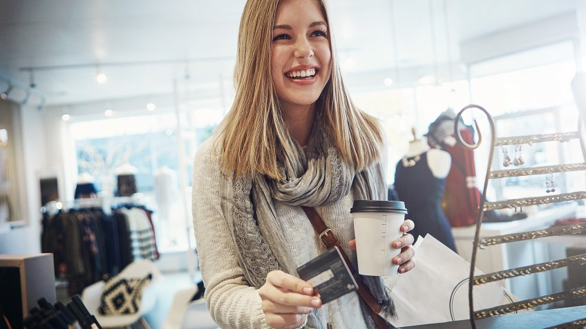 Shot of a young woman ready to pay for her goods in a clothing store.