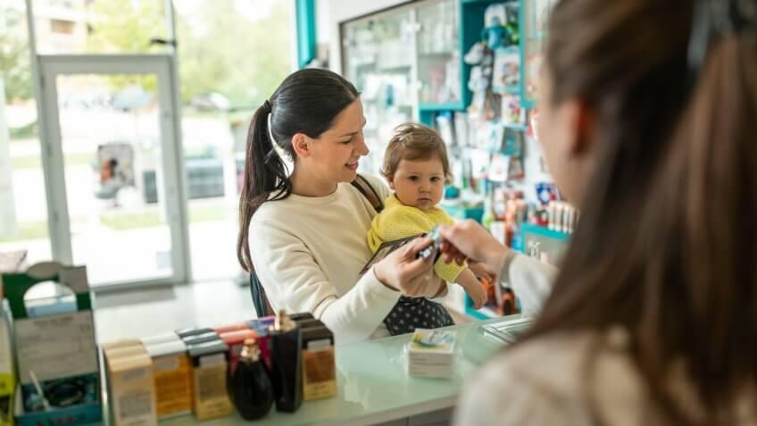 Caucasian mom talks with pharmacist.