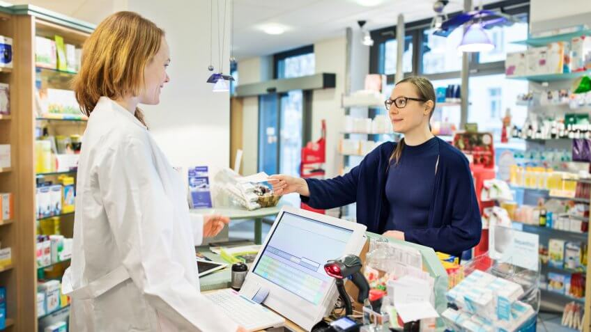 Woman giving prescription to female pharmacist in store.
