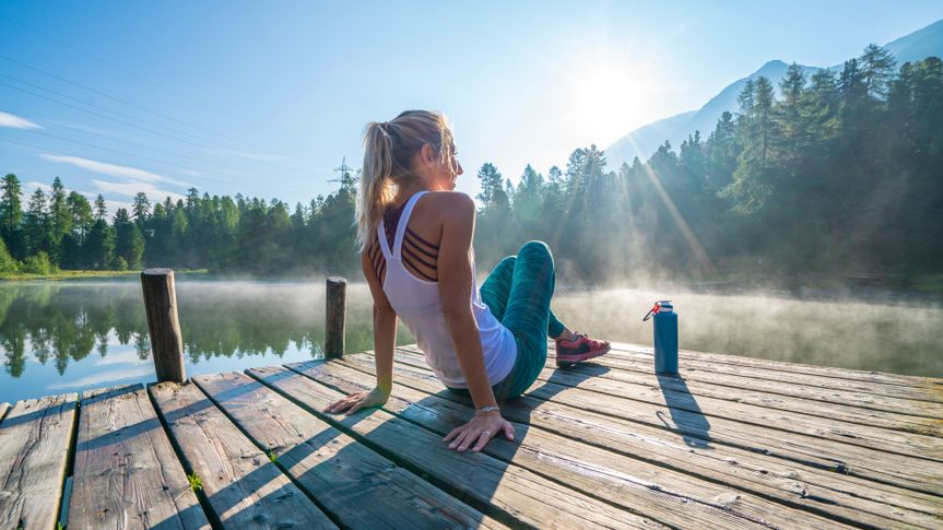 Young woman relaxing before morning jogging, sunrise over beautiful peaceful lake in nature, female standing on pier over waterShot in Graubunden Canton, Switzerland.