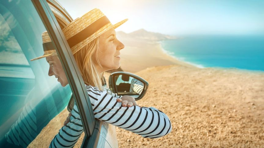 Happiness young woman sitting in her white car and look on the beautifull ocean coastline view.