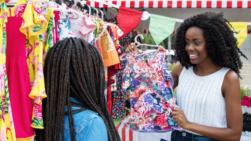 African american woman presenting colorful clothes outdoors at typical traditional market.