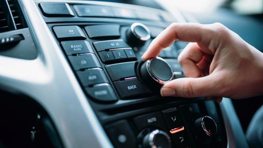 Closeup of young woman hand control radio volume.