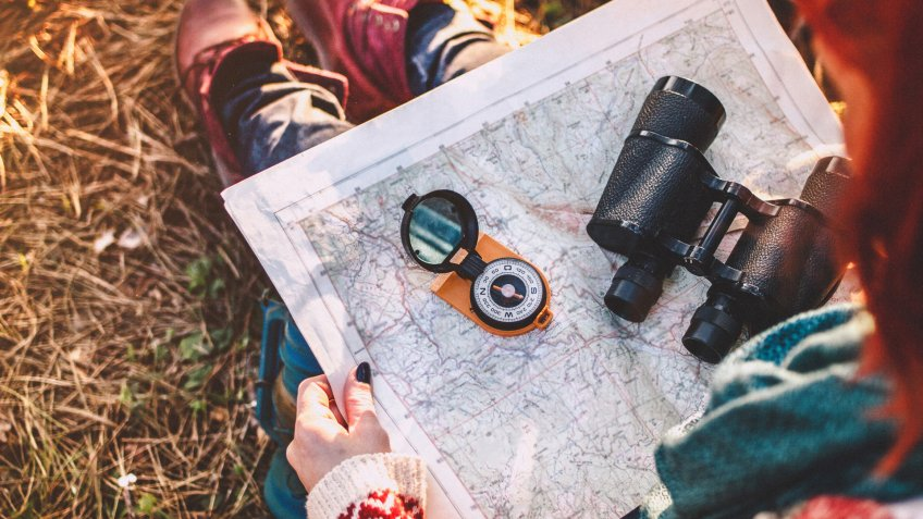 Traveler young woman searching direction with a compass on background of map in the forest.