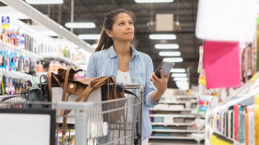 A mid adult woman purses her lips in concentration as she looks for an item on the shelf at the supermarket.
