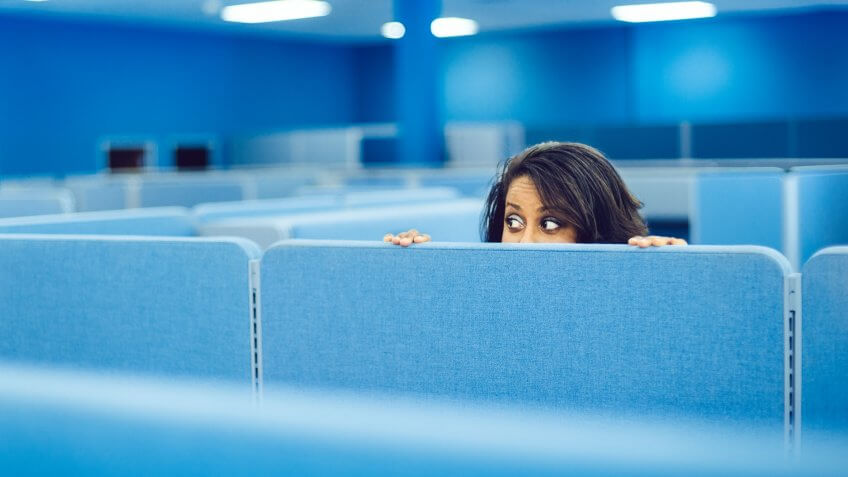 Office worker eavesdropping in cubicle room.