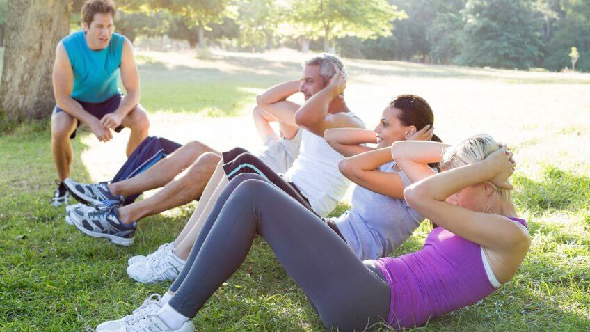 people exercising in park with trainer