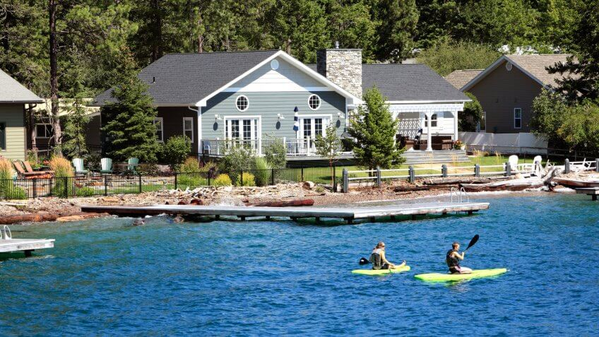 Bigfork,Montana,USA - August 18,2019: Two young people,male and female on paddle boards in front of modern waterfront homes.