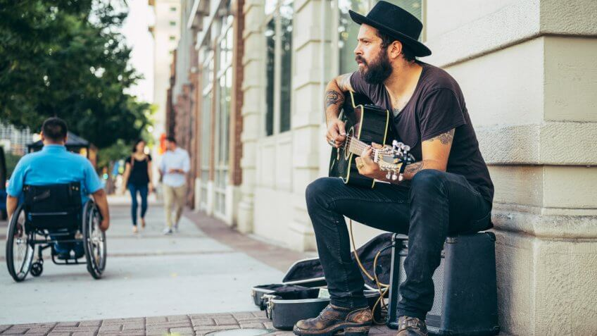A busker street musician playing music for tips on a city sidewalk.