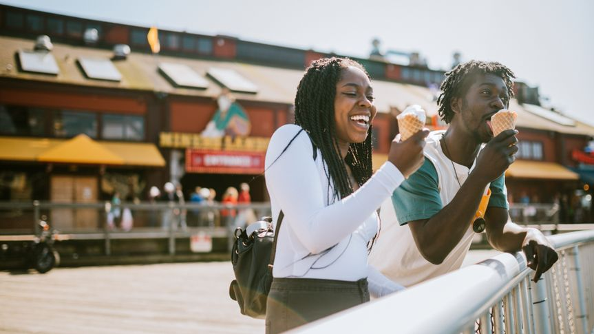 A cute young man and woman enjoy a tasty ice cream waffle cone on a sunny day in downtown Seattle.