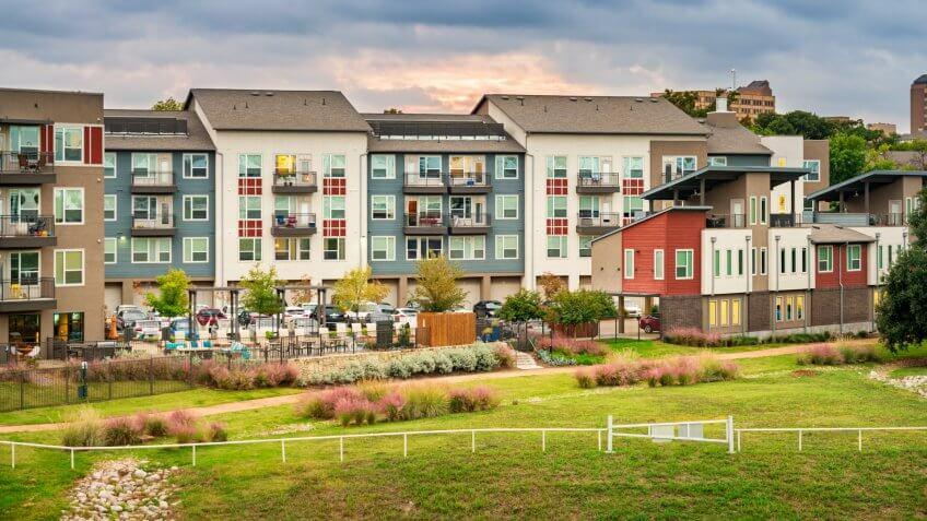 Stock photo of condominium apartment buildings with parking lot and back yard in Dallas, Texas, USA.
