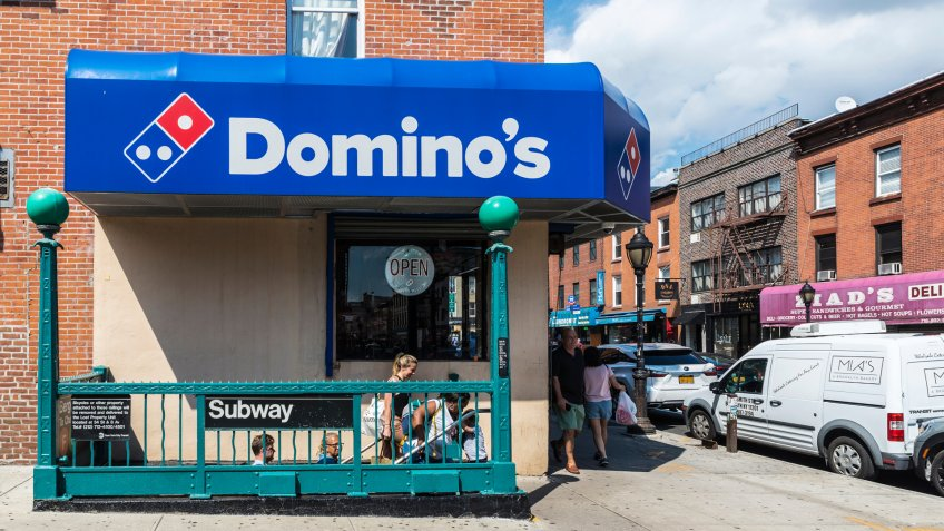 New York City, USA - July 26, 2018: Domino´s Pizza next to a subway station with people around in Brooklyn, Manhattan, New York City, USA.