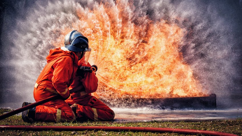 Firefighter in fire fighting suit spraying water, Firemen fighting  raging fire with huge flames of burning, Fire prevention and extinguishing concept.