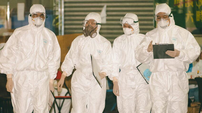 GEAR Health Officials in cover-all protective gear against a mysterious flu-like illness walk outside Hong Kong's Amoy Gardens .