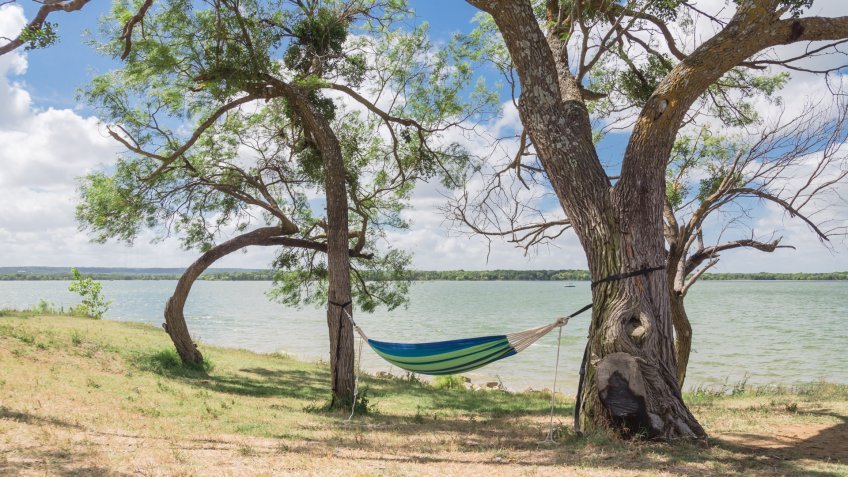 Empty green hammock in shade tree shades at lakeside park in Grand Prairie, Texas, USA.