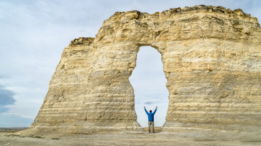 arch in Monument Rocks (Chalk Pyramids) in western Kansas with a human figure added for a scale.