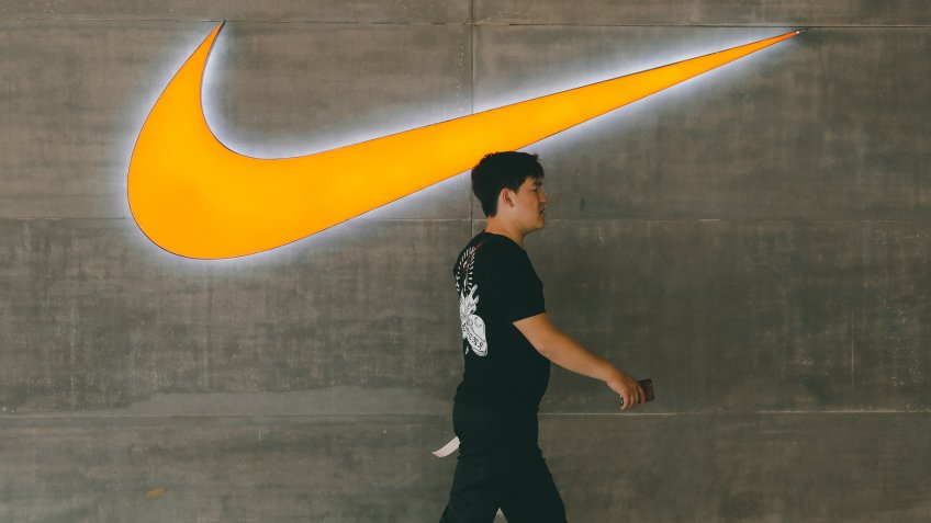 A Chinese man walks past a logo of Nike outside Nike store in Beijing, China, 22 May 2019.