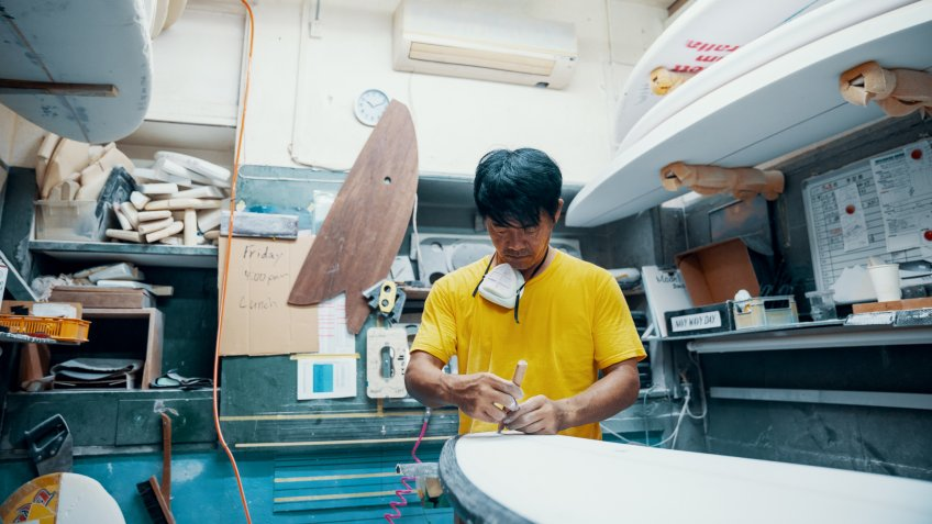 Mature man making and shaping a surfboard in his small business surf shop.