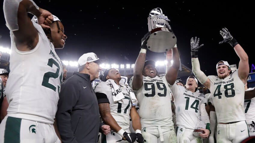 Mandatory Credit: Photo by Frank Franklin II/AP/Shutterstock (10513763q)Michigan State's Raequan Williams (99) holds up the trophy after the team's Pinstripe Bowl NCAA football game against Wake Forest, in New York.