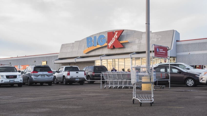 Moorhead, Minnesota, United States - December 7, 2015: Exterior of Big Kmart entrance with parking lot, with shopping carts in foreground.
