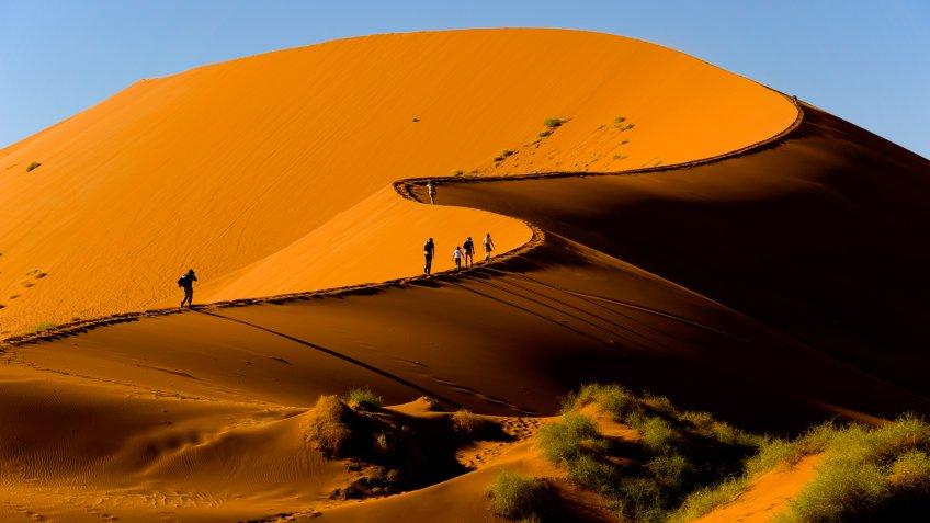 Tourists climbing Sossusvlei dune, Naukluft National Park, Namibia.
