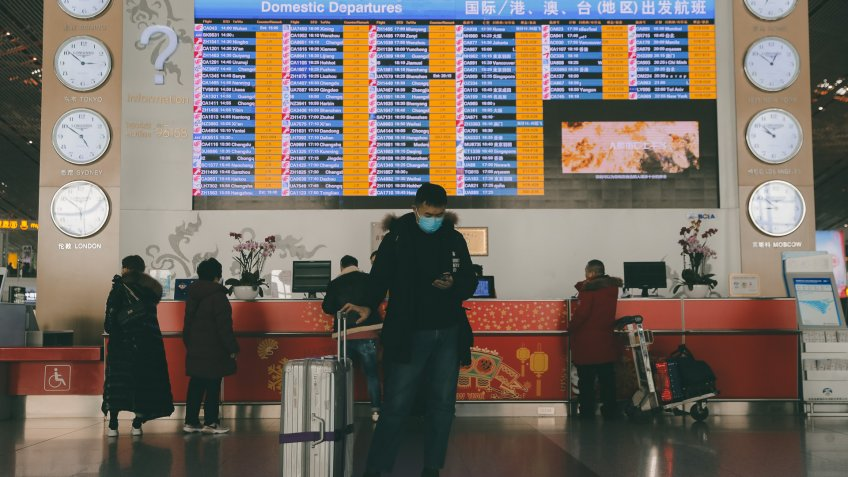 A passenger wears mask standing in front of a departure information screen at terminal 3 of Beijing Capital International Airport in Beijing, China, 26 January 2020.