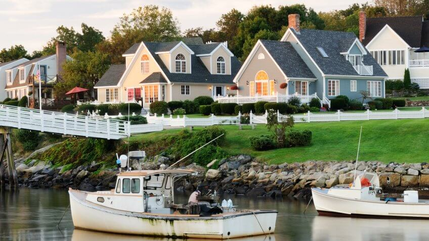"""""""Fishing boats with houses in background at sunrise, blurred water by long exposure, square picture (Perkins Cove, Ogunquit, Maine USA)."""