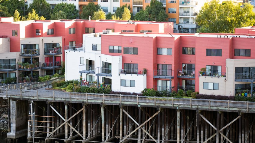 """Painted three-story residential apartments with flat roof built on wooden stilts on the banks of the Willamette River in downtown Portland """"u2013 nice place to living in popular waterfront area."""