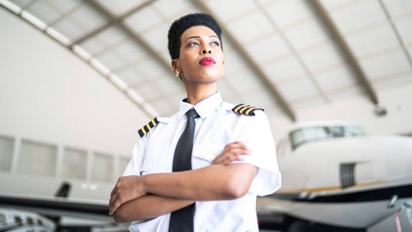 Portrait of airplane pilot in a hangar and looking at camera.