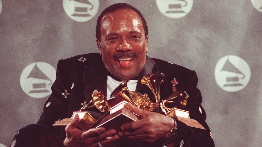 """Quincy Jones cradles his Grammy awards,including the album of the year award, for his eclectic album """"Back on the Block"""" during the 33rd annual Grammy Awards ;at New York's Radio City Music Hall night of Feb."""