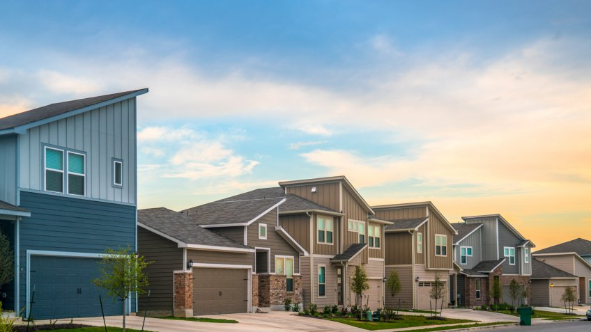 Real Estate Suburb New Development in Austin , Texas , USA - evening afternoon sunset bright sunshine on front yards and facade of new homes in Central Texas Neighborhood.