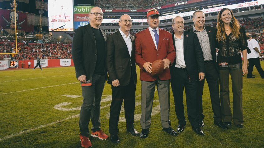 Former Tampa Bay Buccaneers head coach Jon Gruden, center, poses with Glazer family members, owners of the team, after being inducted into the Buccaneers Ring of Honor during halftime of an NFL football game against the Atlanta Falcons, in Tampa, FlaFalcons Buccaneers Football, Tampa, USA - 18 Dec 2017.