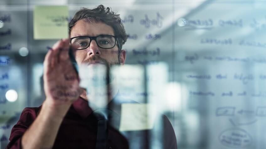 Shot of a young businessman brainstorming with sticky notes on a glass wall in a modern office.
