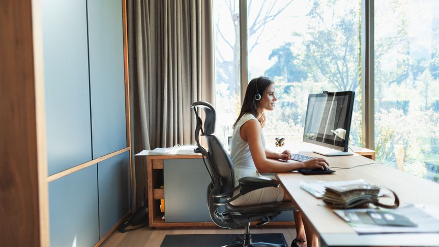 Businesswoman working at computer in home office.