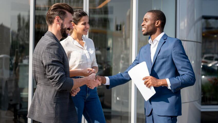 Portrait of a couple of happy customers closing a deal with a salesman at a car dealership and looking very happy handshaking.