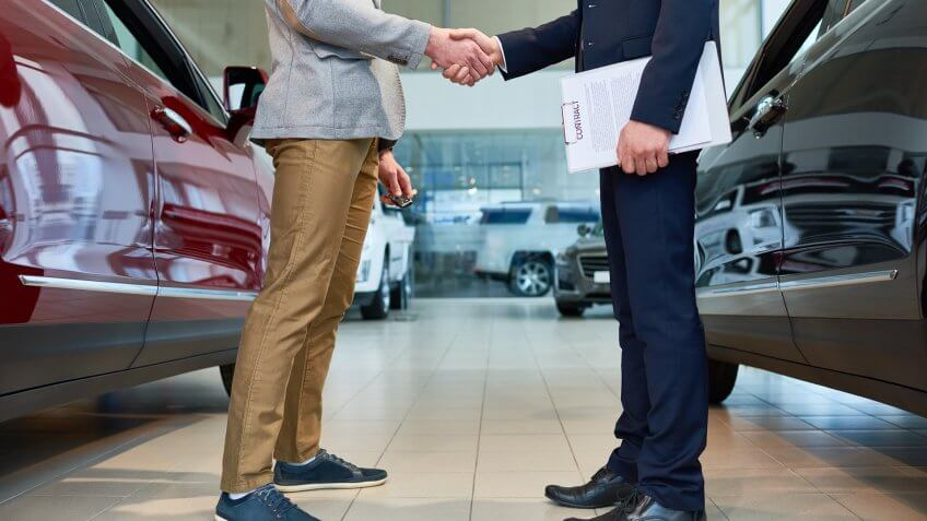 car dealer shaking hands with customer