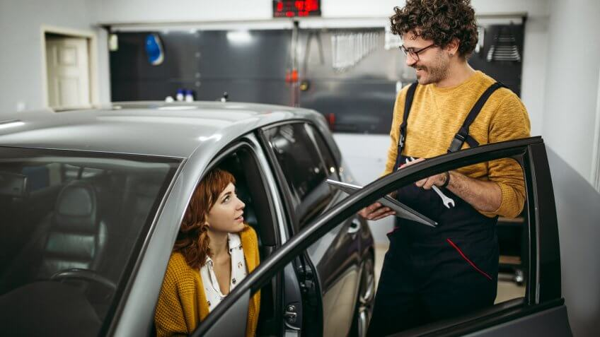 Repairman solving the car problems with a female customer in the car workshop.