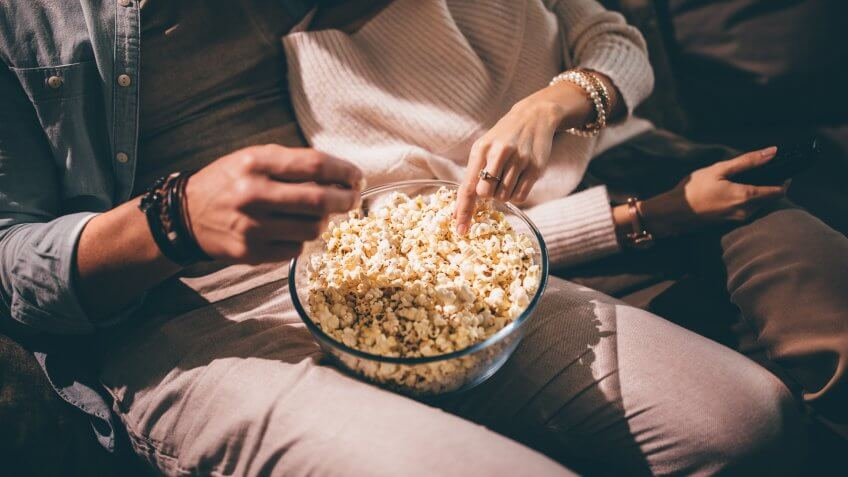 Close-up of chic couple's hands watching television and eating popcorn at night.