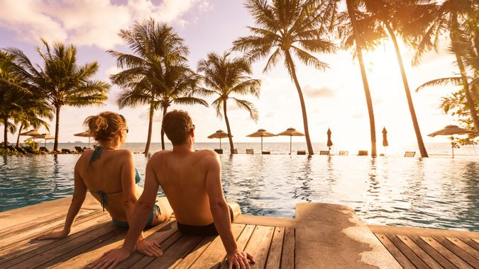 Couple enjoying beach vacation holidays at tropical resort with swimming pool and coconut palm trees near the coast with beautiful landscape at sunset, honeymoon destination.