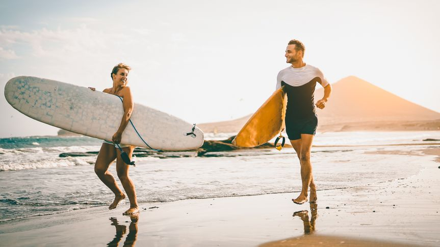 Young couple of surfers running with surfboards on the beach at sunset - Happy lovers going to surf together - People, sport and lifestyle concept - Vintage filter - Focus on woman board.