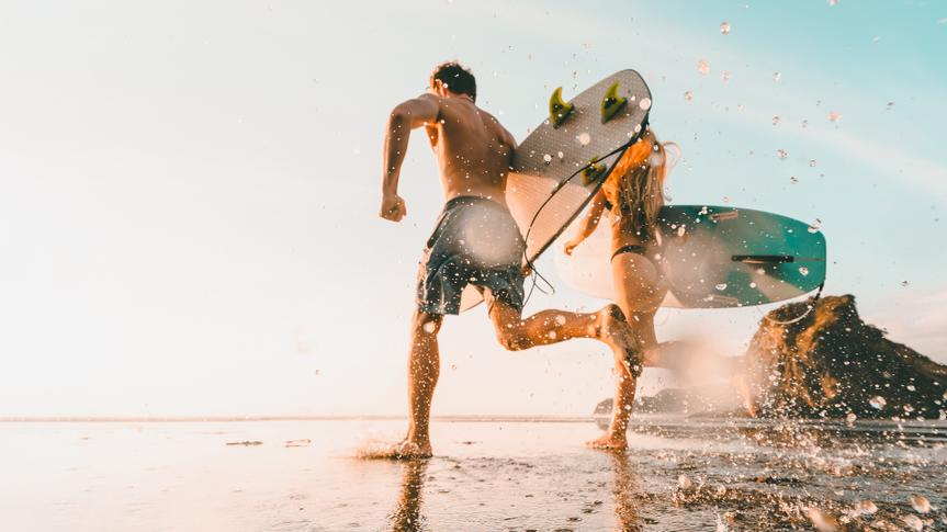 Couple holding surfboards and running towards beach for surfing at Piha Beach, Auckland, New Zealand.