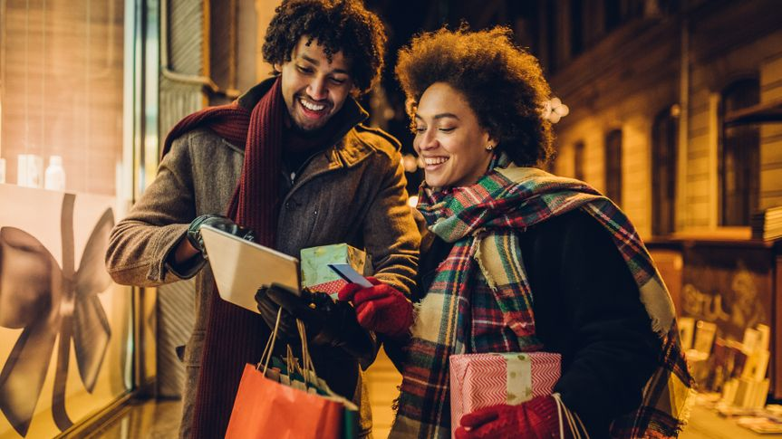Smiling young couple buying Christmas presents online using a credit card and a digital tablet.