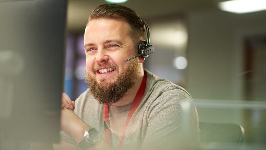 a call centre phone operative in his mid 30s chats on the phone at his desk .