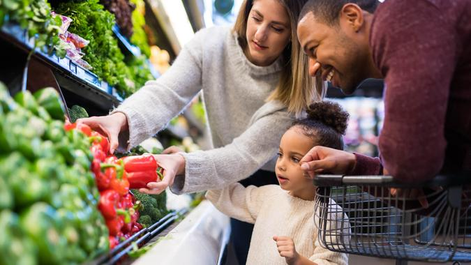 A pre-school age girl helps her parents pick out veggies in the produce section at the grocery store.