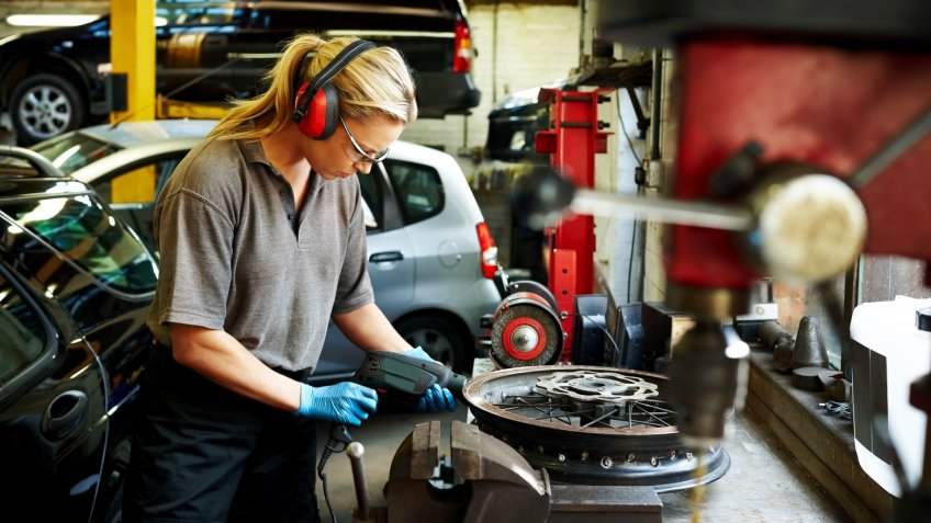 Female mechanic working on car rims in auto garage.