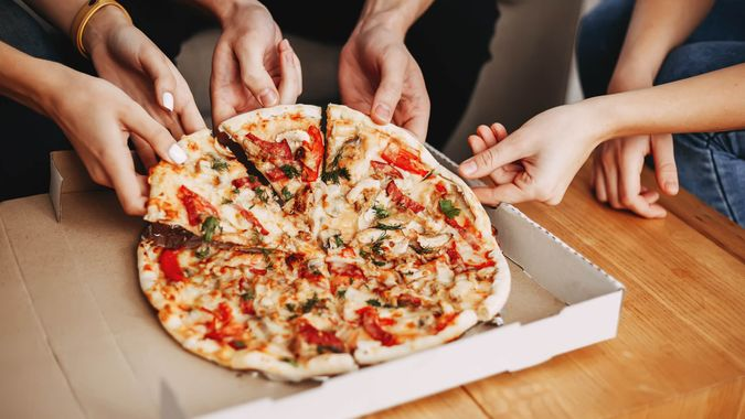 Hands of young people taking pizza slices from delivery box dining together, millennial friends sharing meal having lunch at home, food delivery concept.