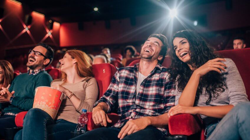 Happy four friends at cinema together.