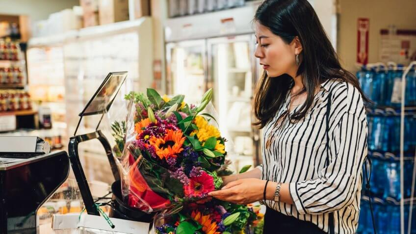 Young asian woman holding beautiful fresh blossom colorful flowers in supermarket.
